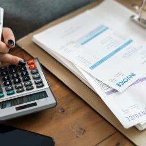 mulher fazendo contas com uma calculadora