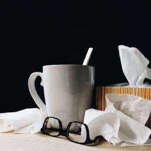 mesa com caneca, lenços de papel e óculos