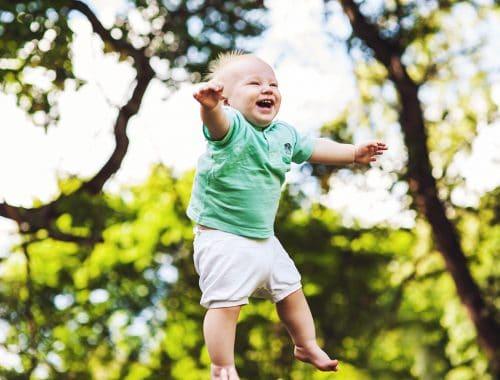 bebê feliz com árvores no fundo