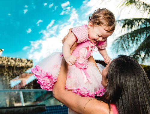 mãe levantando filha que sorri