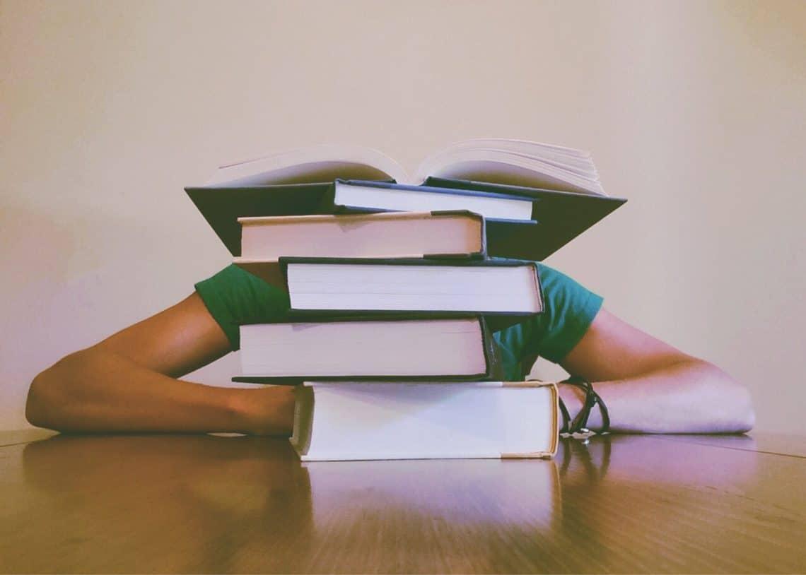 livros empilhados na frente de uma pessoa