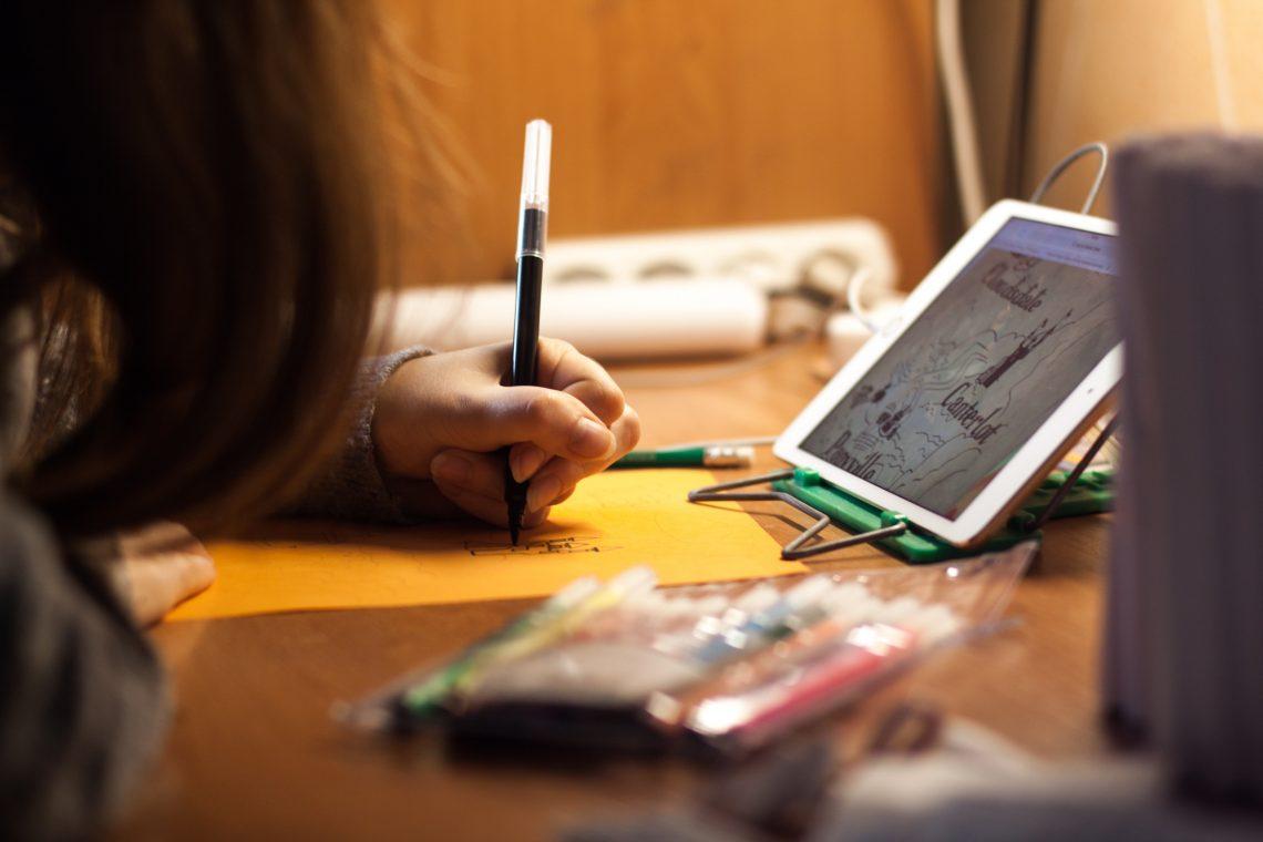 criança desenhando e vendo um tablet