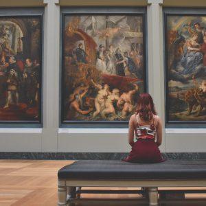 mulher sentada dentro de um museu de frente para três obras de arte