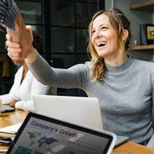 mulher sentada com uma computador a apertando a mão de alguem