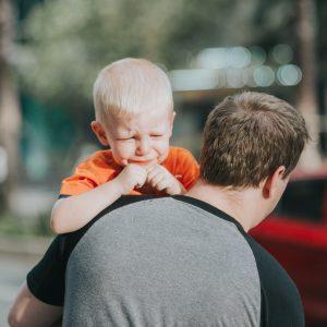 bebê chorando no colo de um pai