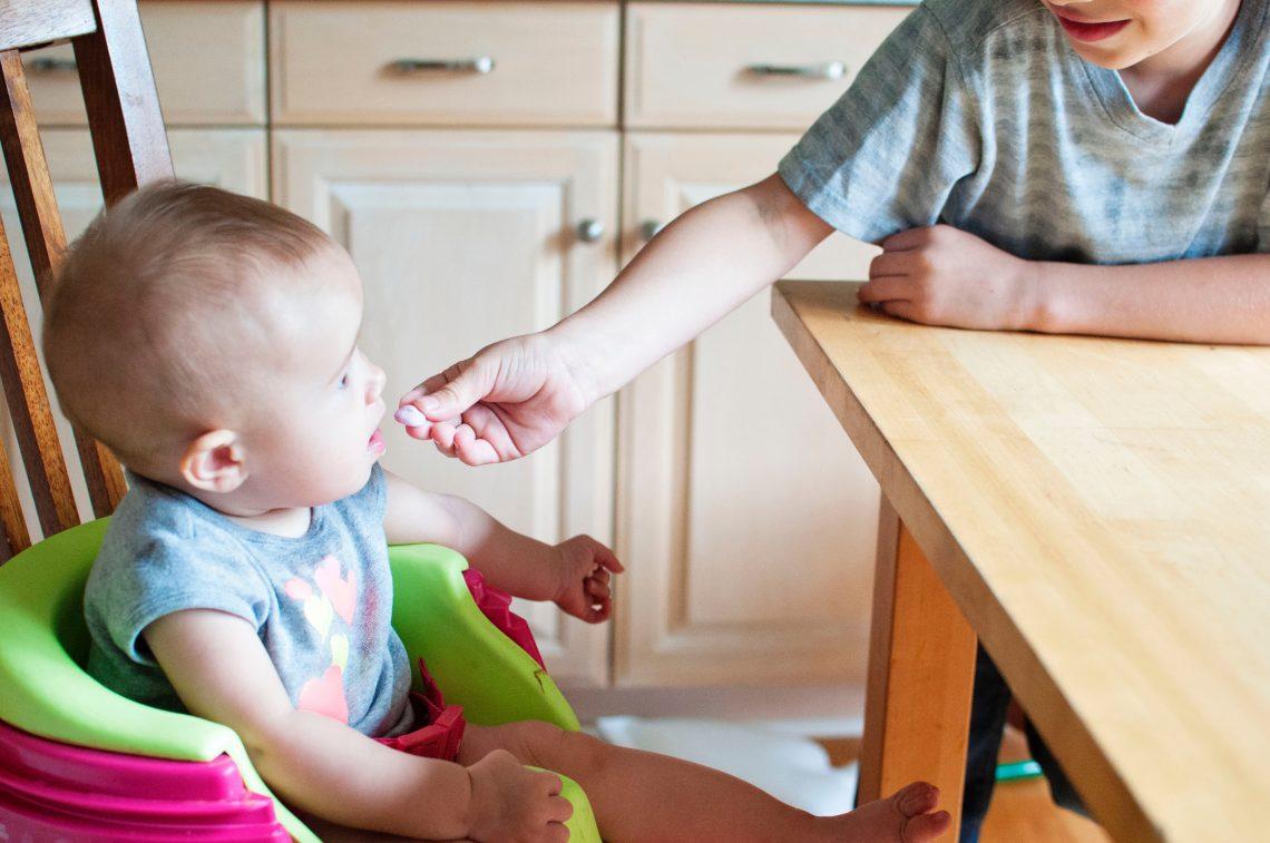 alguém dando comida na boca de um bebê