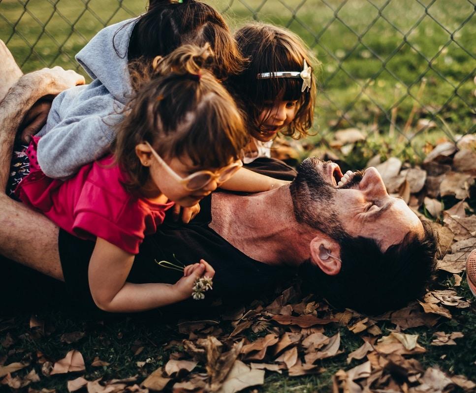 pai com filhas rindo abraçados no chão