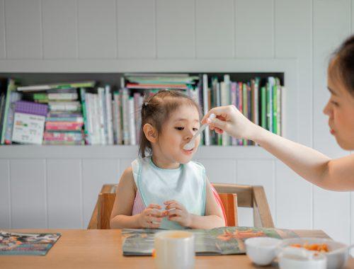 mãe dando papinha para uma criança