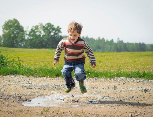 criança pulando na poça de agua