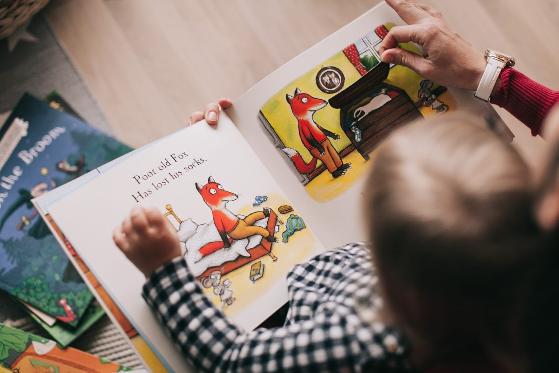 criança loira lendo livro sobre uma raposa