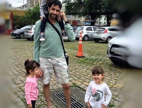 Pai com crianças em um estacionamento