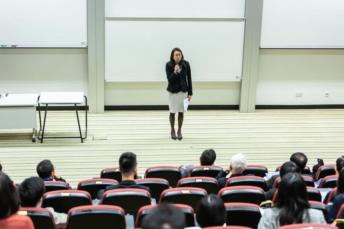 mulher ensinando na frente de um publico
