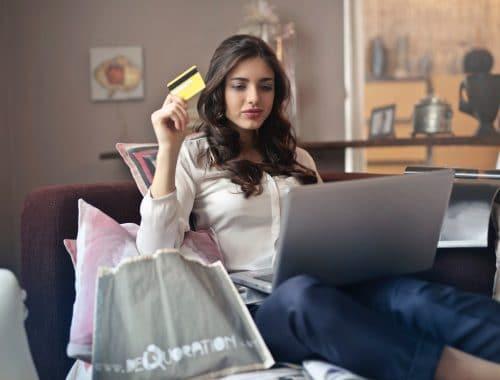 mulher segurando um cartão de credito e fazendo compras pela internet