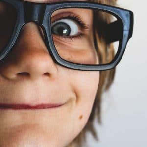 criança de óculos olhando com cara de diversão