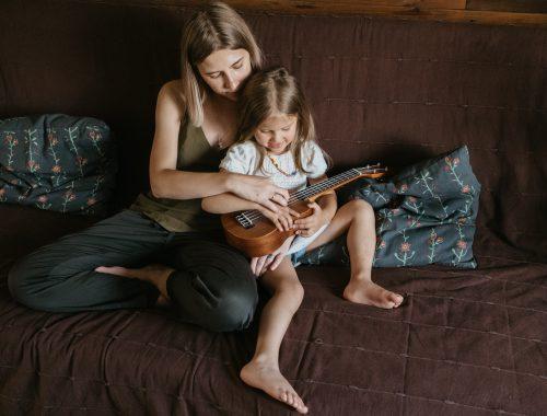 mulher ensinando criança a tocar violão