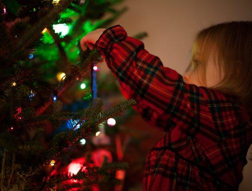 criança mexendo em arvore de Natal