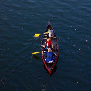 vista aérea de pai e dois filhos em boto em um lago