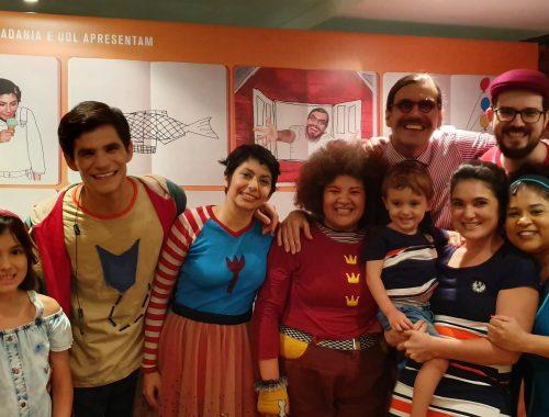 Crianças e adultos tirando foto com personagens de teatro