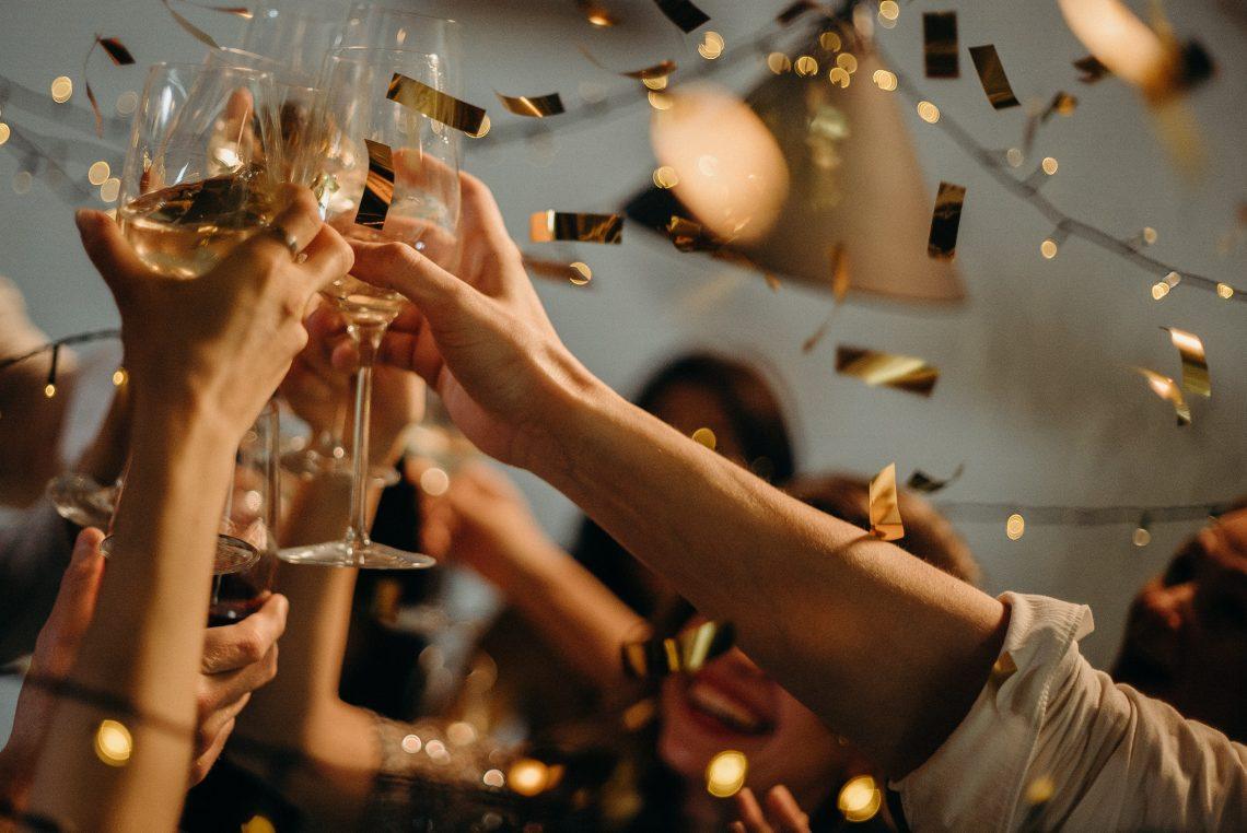 pessoas levantando taças de champagne