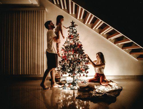 família enfeitando a árvore de Natal