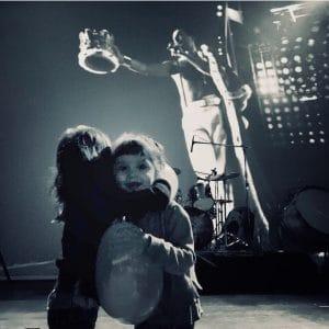 Criança em colo de mulher assistindo a um show de rock