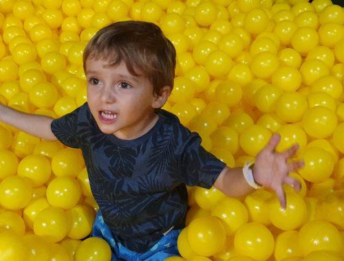 criança em uma piscina de bolinha amarela